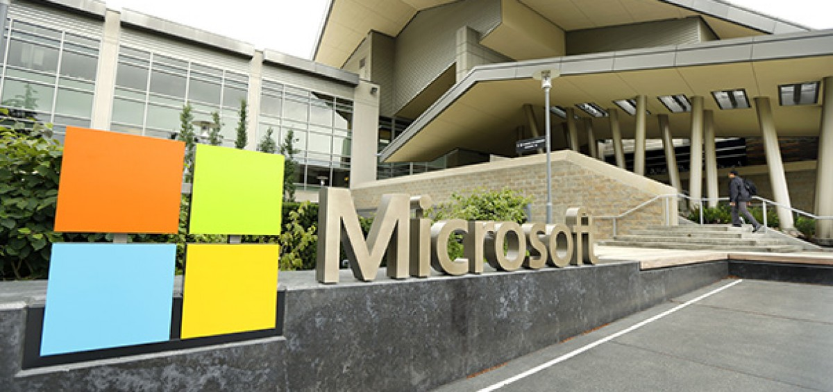 This July 3, 2014 photo shows Microsoft Corp. signage outside the Microsoft Visitor Center in Redmond, Wash. Microsoft on Thursday, July 17, 2014 announced it will lay off up to 18,000 workers over the next year. (AP Photo Ted S. Warren)